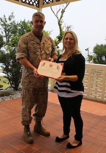 Brig. Gen. Paul J. Kennedy, left, presents Sara Britton with a certificate of appreciation for her dedicated work as a family readiness assistant for 3rd Marine Expeditionary Brigade April 30 at Camp Courtney. As a family readiness assistant, Britton served 153 hours, working hand-in-hand with the family readiness officer to assist service members and families of 3rd MEB, III Marine Expeditionary Force. Britton is a Portland, Maine native. Kennedy is the commanding general of 3rd MEB.
