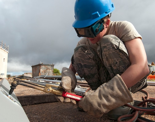 H.E. HOLT NAVAL COMMUNICATION STATION, Australia – Staff Sgt. Kelli Naramore, operations manager for the Alaska Air National Guard's 176th Civil Engineer Squadron, uses an oxyacetylene torch to cut a hole in a girder here May 6, 2014. Thirty-four Alaska Air Guard members, most from the 176th CES, deployed for two weeks to this tiny outpost at the far western tip of Australia to help build a space radar facility to be jointly operated by Australia and the United States. U.S. Air National Guard photo by Capt. John Callahan/ Released.