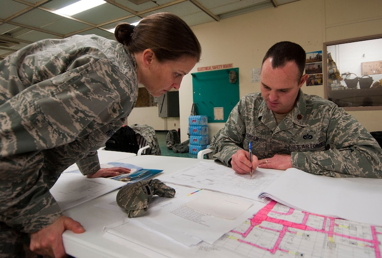 H.E. HOLT NAVAL COMMUNICATION STATION, Australia – Maj. Kim Riggs, construction flight chief for the Alaska Air National Guard's 176th Civil Engineer Squadron, and Maj. Chris Mercer, the squadron's infrastructures flight chief, study blueprints for the facility here May 6, 2014. The two were among thirty-four Alaska Air Guard members, most from the 176th CES, who deployed for two weeks to this tiny outpost at the far western tip of Australia to help build a space radar facility to be jointly operated by Australia and the United States. National Guard photo by Capt. John Callahan.