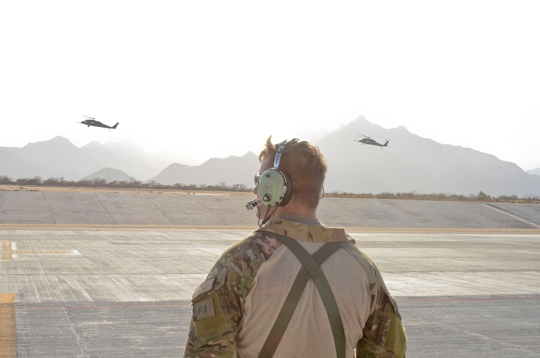 U.S. Air Force Master Sgt. Chris Young, 48th Rescue Squadron Pararescueman, observes two 55th RQS HH-60G Pavehawks prepare to land at Cabo San Lucas International Airport, Mexico, May 5, 2014. The Pavehawks conducted four hoist operations to extract two injured sailors and six Guardian Angels from a ship 540 nautical miles off the Pacific coast of Mexico. A 79th RQS HC-130J Combat King II then transported mission essential personnel to Naval Air Station North Island, Calif. (U.S. Air Force photo by Staff Sgt. Adam Grant/Released)
