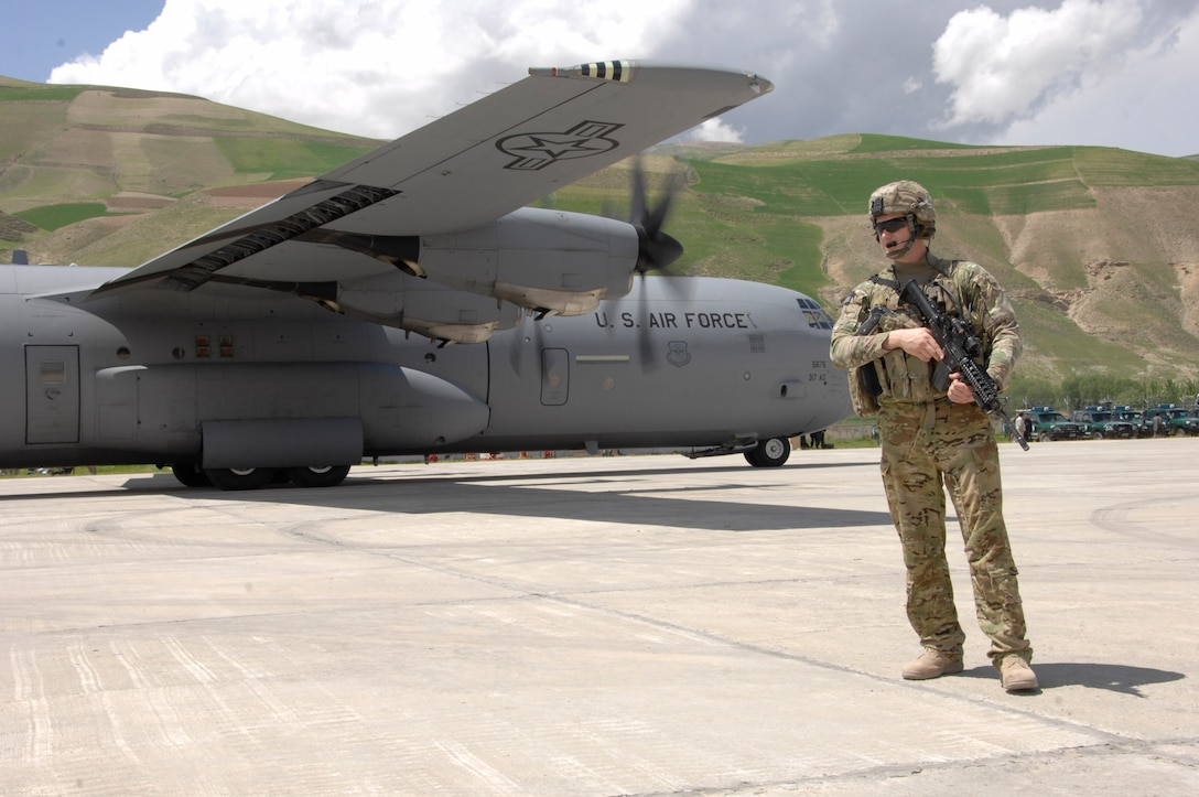 FAYZABAD, Afghanistan - U.S. Air Force Senior Airman Shawn Donovan, a Fly Away Security Team member assigned to the 455th Expeditionary Base Defense Squadron, Bagram Airfield, Afghanistan and a native of Swansboro, N.C., stands guard as C-130 J-30 is unloaded with personnel and supplies at Fayzabad Airport May 5, 2014. Coalition Forces to include an Italian C-130 and a crew assigned to the 774th Expeditionary Airlift Squadron assisted the Afghan Government with relief efforts after a recent mudslide in Badakhshan province. (U.S. Air Force photo by Master Sgt. Cohen A. Young)