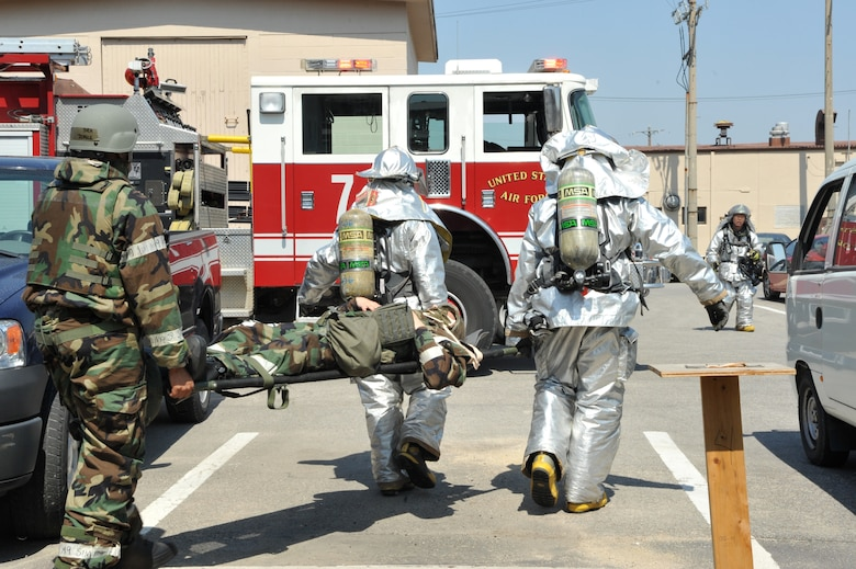 Firefighters from the 51st Civil Engineer Squadron help a member of Bldg. 938's post-attack reconnaissance team carry a mock casualty to a casualty collection point during Operational Readiness Exercise Beverly Bulldog 14-02 at Osan Air Base, Republic of Korea, May 6, 2014. First responders assisted the building's post-attack reconnaissance teams with the triage and transport of mock casualties during the ORE scenario. (U.S. Air Force photo/Airman 1st Class Ashley J. Thum)