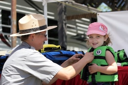 Amber Machado, a ranger at Black Butte Lake, the U.S. Army Corps of Engineers Sacramento District park near Orland, Calif., presents an eager young visitor with her new life jacket during the 2013 Life Jacket Trade-in event.