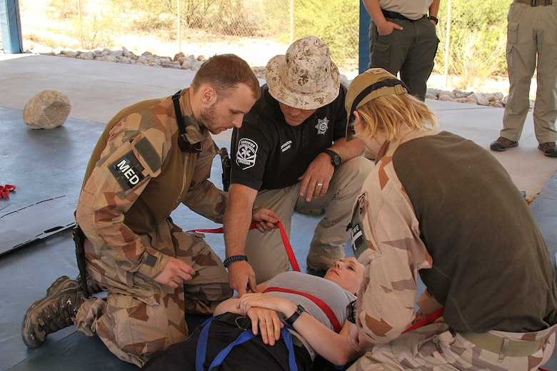 Russ Dodge, Arizona Department of Public Safety Police Officer Paramedic, teaches Lance Cpls. Klas Persson and Tobeas Lofberg, Swedish Air Force Rangers, how to secure an injured person to a litter during Tactical Combat Casualty Care training at the Pima County Training Center in Tucson, Ariz., May 6, 2014. TCCC introduces evidence-based, life-saving techniques and strategies for providing the best trauma care on the battlefield.  TCCC is a training event held during Exercise ANGEL THUNDER.  Exercise ANGEL THUNDER is a multilateral annual exercise that to supports DoD's training requirements for Personnel Recovery responsibilities through high–fidelity exercises. Exercise ANGEL THUNDER provides the most realistic PR training environment available to USAF Rescue forces, as well as their Joint, Interagency, and Coalition partners. Exercise ANGEL THUNDER is collaborating with AF Special Operations Command's Emerald Warrior exercise and the US Navy 3rd Fleet Joint Warfighting Center training and exercises.   (U.S. Air Force photo by Tech. Sgt. Heather R.Redman/Released)