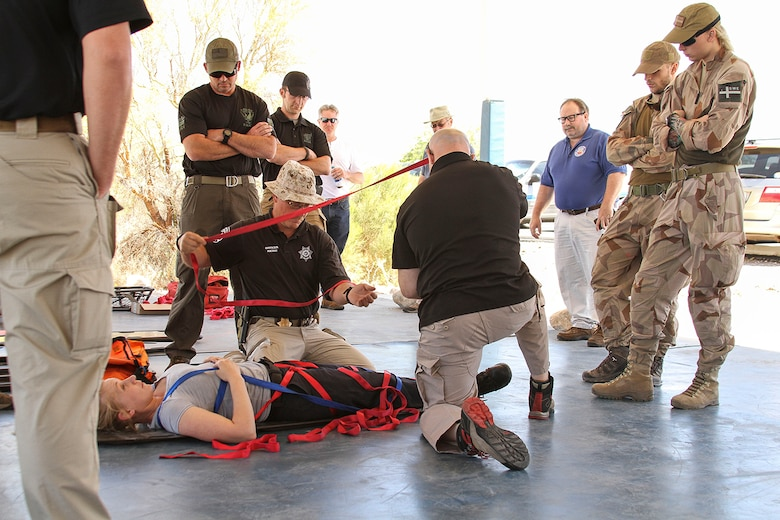 Members from the U.S. Secret Service, Swedish Air Force, Air Evacuation Services, and local police departments practice securing an injured person to a litter during Tactical Combat Casualty Care training at the Pima County Training Center in Tucson, Ariz., May 6, 2014. TCCC introduces evidence-based, life-saving techniques and strategies for providing the best trauma care on the battlefield.  TCCC is a training event held during Exercise ANGEL THUNDER.  Exercise ANGEL THUNDER is a joint-interagency-coalition annual exercise that supports DoD's training requirements for Personnel Recovery responsibilities through high–fidelity exercises. Exercise ANGEL THUNDER provides the most realistic PR training environment available to USAF Rescue forces, as well as their Joint, Interagency, and Coalition partners. (U.S. Air Force photo by Tech. Sgt. Heather R.Redman/Released)