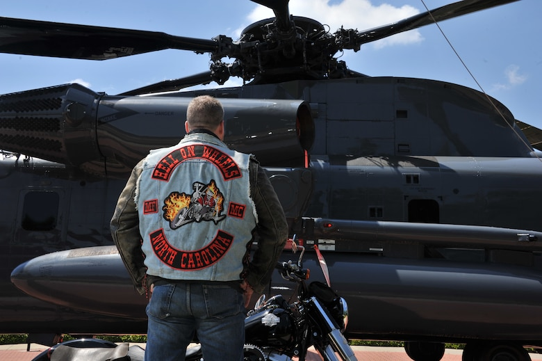 William Dulaney, professor of organizational communication at the Air Force Culture and Language Center, and a faculty member of the Air University Air War College, looks at an HH-53 Super Jolly Green Giant static display on his Harley, at Maxwell Air Force Base. Dulaney spent his military career in a variety of positions, including the Special Forces, and is a member of the Biker culture and a member of a motorcycle club. . He is getting ready to deploy for his third one-year tour in Afghanistan as an advisor to the U.S. military forces there on a mission to support the transition of operations and leadership to the Afghan government. (U.S. Air Force photo by Staff Sgt. Gregory Brook)