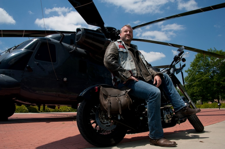 William Dulaney, professor of organizational communication at the Air Force Culture and Language Center, and a faculty member of the Air University Air War College, poses in front of an HH-53 Super Jolly Green Giant static display on his Harley, at Maxwell Air Force Base. Dulaney, a former missiles troop and later a Special Forces airman, is one of the world's foremost authorities on the biker subculture and advises the Air Force on intercultural communication. He is getting ready to deploy for his third one-year tour in Afghanistan as an advisor to the U.S. military forces there on a mission to support the transition of operations and leadership to the Afghan government. (U.S. Air Force photo by Staff Sgt. Gregory Brook)
