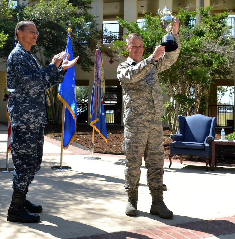 Adm. Cecil D. Haney, commander, U.S. Strategic Command, looks on as Col. William Poirier, 67th Cyberspace Wing Commander, hoists the 2013 Global Operations Omaha Trophy. The Omaha Trophy is awarded annually to four outstanding units that represent USSTRATCOM's mission areas, their role in global operations and USSTRATCOM's continued emphasis on strategic deterrence. (U.S. Air Force photo by Master Sgt. Drew Nystrom/Released)