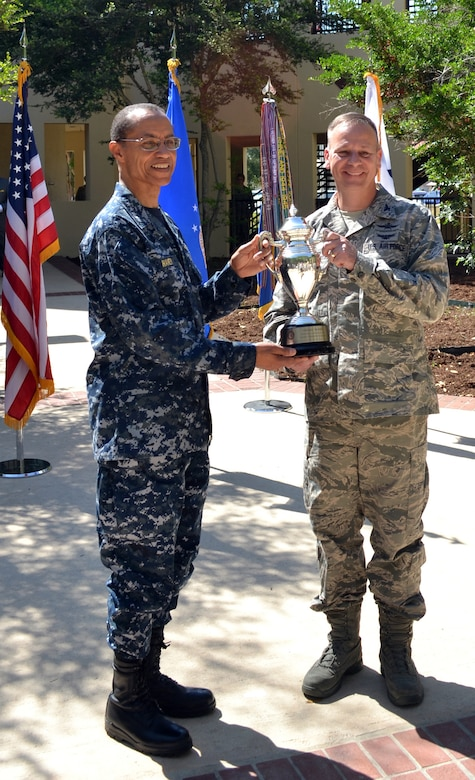 Adm. Cecil D. Haney, commander, U.S. Strategic Command, awards the 2013 Global Operations Omaha Trophy to Col. William Poirier, 67th Cyberspace Wing Commander. The Omaha Trophy is awarded annually to four outstanding units that represent USSTRATCOM's mission areas, their role in global operations and USSTRATCOM's continued emphasis on strategic deterrence. (U.S. Air Force photo by Master Sgt. Drew Nystrom/Released)