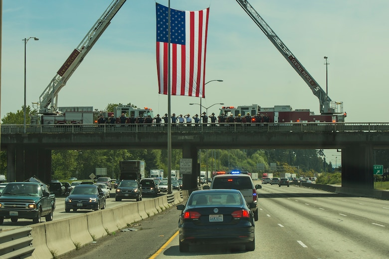 Central Pierce and Joint Base Lewis-McChord firefighters salute the procession of Air Force Capt. Douglas D. Ferguson's remains May 1, 2014, on an overpass in Tacoma, Wash. Ferguson, a Tacoma native, was killed while on a reconnaissance mission over Laos when his aircraft was shot down Dec. 30, 1969. (U.S. Air Force photo/Tech. Sgt. Sean Tobin)