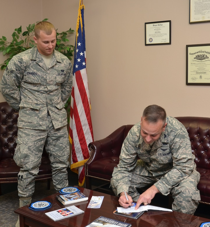 Col. William Poirier (right), 67th Cyberspace Wing commander, participates in the Air Force Assistance Fund donation campaign after being briefed by the wing's AFAF representative, Airman 1st Class Craig D'Angelo (left) May 6. (U.S. Air Force photo by:  24th Air Force Public Affairs)