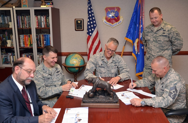 Col. Michael Harasimowicz, 688th Cyberspace Wing commander (center); Col. Dean Clothier (center left), 688th CW vice commander; J. Michael Kretzer (far left), 688th CW technical director; and Chief Master Sgt. William Jones, 688th CW command chief, make contributions to the Air Force Assistance Fund while AFAF representative Staff Sgt. Matthew Sims looks on. (U.S. Air Force photo by:  24th Air Force Public Affairs)