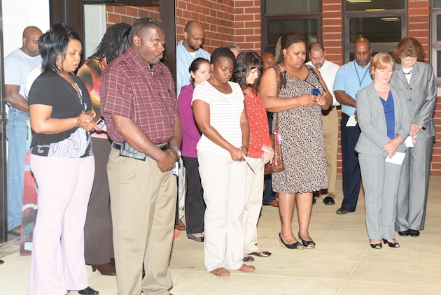 Base employees pray silently during the National Day of Prayer ceremony in front of Coffman Hall, May 1, 2014.