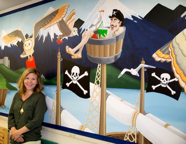 Gwyn Korpi, a military spouse and graphic designer, stands near a mural she painted at the at the children's area of the Harriotte B. Smith Library aboard Marine Corps Base Camp Lejeune. The mural is designed to pique children's interests with a fairy tale world that could be the setting of many works of children's fiction.