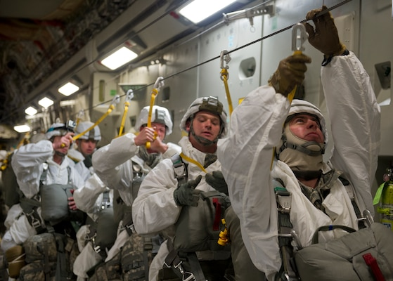 Army Maj. Aaron Williams (right), 2nd Engineer Brigade, 6th Engineer Battalion (Combat)(Heavy), battalion executive officer, secures his static line to his parachute before jumping out of a C-17 Globemaster III during Arctic Pegasus, May 1, 2014. Arctic Pegasus is a multi-component, joint exercise that will further refine planning and mission capabilities between U.S. Army Alaska, the U.S. Air Force, the Alaska National Guard, and the state of Alaska. (U.S. Air Force photo/Staff Sgt. Zachary Wolf)