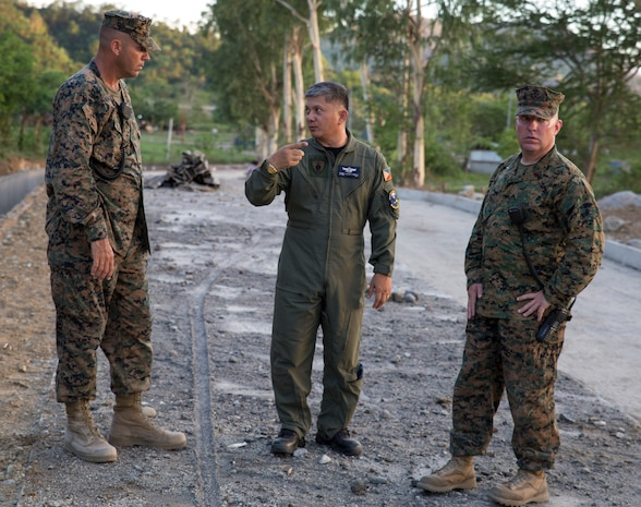 Philippine Air Force Lt. Col. Romell Allan P. Genete, center, the group commander of the 790th Air Base Group, discusses road construction operations with U.S. Marine Corps Chief Warrant Officer 3 Keith W. Earhart, right, and U. S. Marine Corps Master Sgt. Mark D. McLaughlin, left, May 4, 2014, at Crow Valley, Philippines. The Philippine Air Force will team up with U.S. Marines to help relieve traffic hazards outside a major training area of Balikatan 2014. The two nation's militaries will participate in the exercise to increase interoperability and reinforce mission readiness. Earhart and McLaughlin are assigned to 3rd Maintenance Battalion, Combat Logistics Regiment 35, 3rd Marine Logistics Group, III Marine Expeditionary Force.