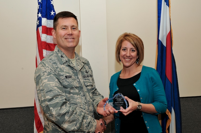 Col. Dan Wright, 460th Space Wing commander, presents the Community Heroes of Buckley Award to Suzanne Pitrusu, the 5th community member to receive this recognition May 8, 2014, at the 140th Headquarters Building on Buckley Air Force Base, Colo. The CHOB program was started in 2011 as a way to recognize community leaders for their outstanding service to Team Buckley. (U.S. Air Force photo by Senior Airman Phillip Houk/Released)