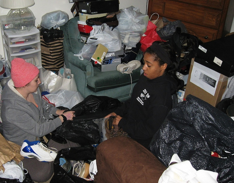 A1Cs Bethany Baines left and Jalynn Wilford both from the 88 Force Support Squadron sit on the bedroom floor surrounded by donated shoes that had to be match and bagged for the Soles4Souls drive. (photo by Ted Theopolos)