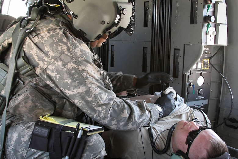 Spc. T.J. Hayer, a medical technician assigned to the 7th Battalion, 158th Aviation Regiment of the Army National Guard, provides simulated medical attention to Sgt. Ryan Swain's sucking chest wound during a simulated casualty evacuation scenario as part of Exercise ANGEL THUNDER at Davis-Monthan AFB, Ariz., May 7, 2014.  ANGEL THUNDER is a multilateral annual exercise that to supports DoD's training requirements for Personnel Recovery responsibilities through high–fidelity exercises.  Exercise ANGEL THUNDER focuses on scenarios that rescue forces are likely to face in current and future contingencies—increasing their combat readiness across a range of military options. (U.S. Air Force photo by Tech. Sgt. Heather R. Redman/Released)