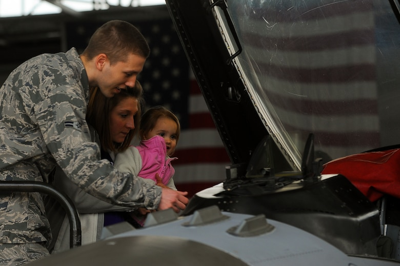 Nicole Tart, spouse of U.S. Air Force 2nd Lt. Lewis Tart, 52nd Maintenance Group assistant officer in charge of maintenance operations, and their daughter McKenley Tart, 2, look at the cockpit of a U.S. Air Force F-16 Fighting Falcon fighter aircraft during a 52nd MXG spouses tour May 8, 2014, at Spangdahlem Air Base, Germany. Spouses toured 52nd MXG facilities to learn how their loved ones contribute to the wing mission. (U.S. Air Force photo by Senior Airman Rusty Frank/Released)