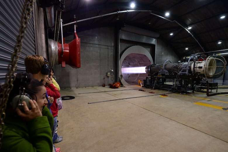 "Military spouses watch a U.S. Air Force F-16 Fighting Falcon fighter aircraft engine run inside the ""Hush House"" during a 52nd Maintenance Group spouses tour May 7, 2014, at Spangdahlem Air Base, Germany. As a part of the tour that was held to celebrate Military Spouse Appreciation Day, the spouses toured many facilities including the ""Hush House,"" sheet metal and fuel barn. (U.S. Air Force photo by Senior Airman Rusty Frank/Released)"