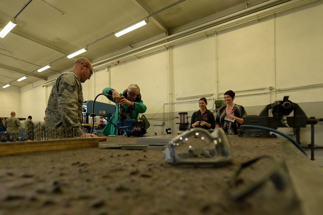 U.S. Air Force Tech. Sgt. Robby Worley, a 52nd Equipment Maintenance Squadron aircraft structural maintenance craftsman form Littlerock, Calif., instructs a spouse how to drill a hole in a piece of sheet metal during the 52nd Maintenance Group spouses tour May 7, 2014, at Spangdahlem Air Base, Germany. As a part of the tour, the spouses saw how the fabrication flight directly affects the base's flying mission. (U.S. Air Force photo by Senior Airman Rusty Frank/Released)