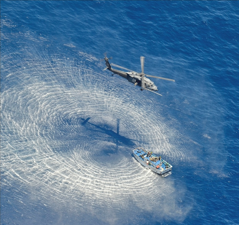 A 55th Rescue Squadron HH-60G Pavehawk helicopter hovers above a skiff to hoist critically burned sailors May 5, 2014, 600 nautical miles off the Pacific Coast of Mexico. The pararescuemen transported the injured sailors to Cabo San Lucas, Mexico, where they were transferred to a HC-130J Combat King II that flew them to the University of California, San Diego, Calif., regional burn unit. (U.S. Air Force photo/ Staff Sgt. Adam Grant)