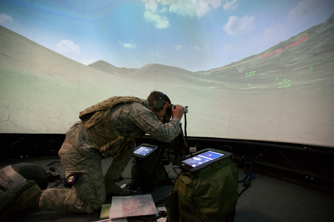 A member of the 146th Air Support Operations Squadron participates in training utilizing the Air National Guard Advanced Joint Terminal Attack Controller Training System to Brig. Gen. Hopper Smith May 7, 2014, during an unveiling of the first operational AAJTS in the nation at Will Rogers Air National Guard Base in Oklahoma City. The AAJTS is a high-fidelity, fully immersive, simulator designed to support Air National Guard Joint Terminal Attack Controller and Combat Controller squadron level continuation, qualification and mission rehearsal training. (U.S. Air Force photo/Maj. Geoff Legler)