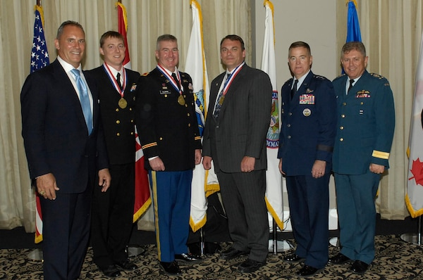 Outstanding NORAD-USNORTHCOM members were recognized during the Missile Warning and Defender of the Year Award Ceremony on May 2nd, 2014 at the Mining Exchange Hotel in Colorado Springs.(l-r) Mr. Rikki Ellison, Founder and Chairman, MDAA, LCDR Tim Ladowicz, Col Fred Clarke, Mr. Jeff Dillemuth, (missing) Lt Col Rickey McCann. They are accompanied by USNORTHCOM Deputy Commander Gen Michael Dubie and NORAD Deputy Commander, Canadian Lt-Gen Alain Parent.