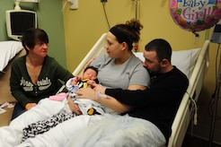 Airman 1st Class Samuel DeWitt (right), and his wife Kaila look to Kaila's mother, Ginger Preston, for parental guidance and support as they share a moment with their newborn daughter Kynnedie at MedStar Southern Maryland Hospital on March 31,2014. DeWitt, 79th Medical Staging Squadron diet therapy apprentice, and Kaila said Preston is their hero. (U.S. Air Force photo / Amber J. Russell)
