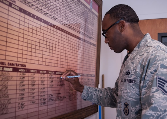 Staff Sgt. Henry Edwards III, 30th Security Forces Squadron military working dog trainer and handler, updates a record board, April 29, Vandenberg Air Force Base, Calif. Detailed records are kept for each MWD to track health and behavior. (U.S. Air Force photo by Airman 1st Class Yvonne Morales/Released)