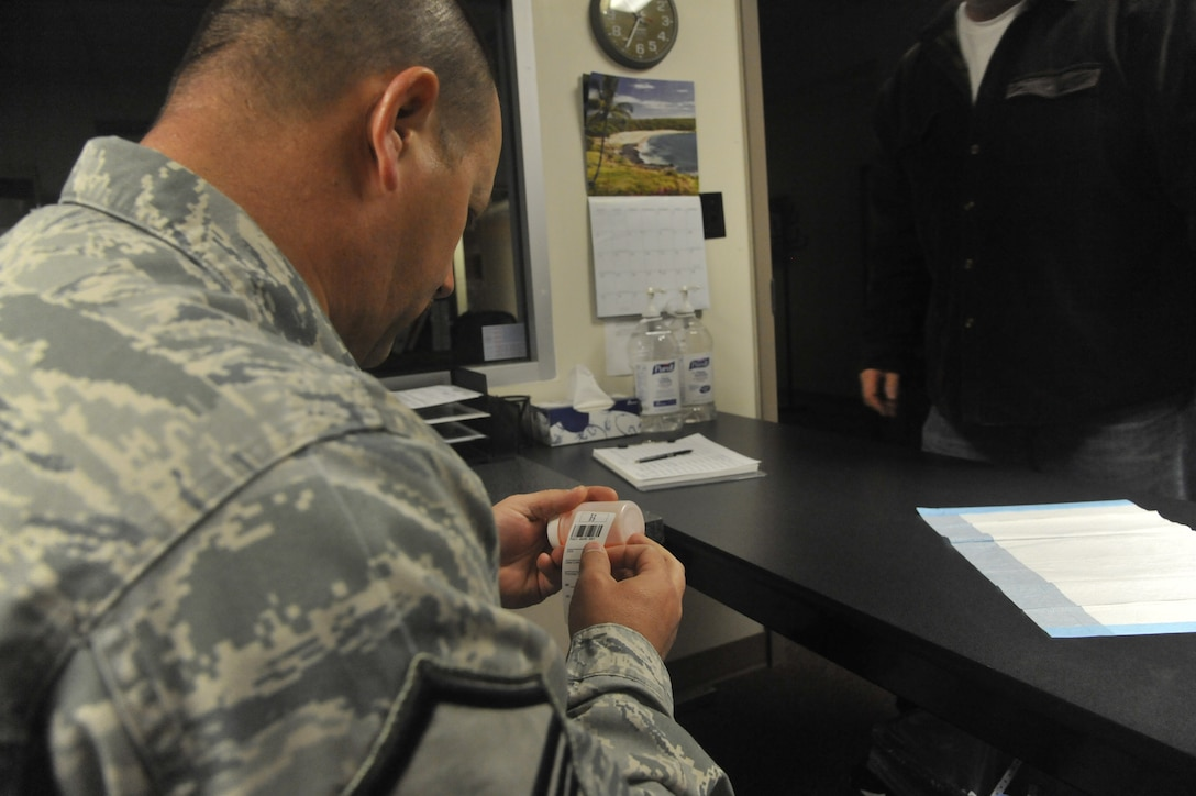 U.S. Air Force Master Sgt. Todd Schafer, 509th Bomb Wing drug testing program administrative manager, places lab label on a member's specimen bottle at Whiteman Air Force Base, Mo., April 30, 2014. This procedure is done to prepare the bottle for collection and shipping to Lackland Air Force Base, Texas. (U.S. Air Force photo by Airman 1st Class Keenan Berry/Released)