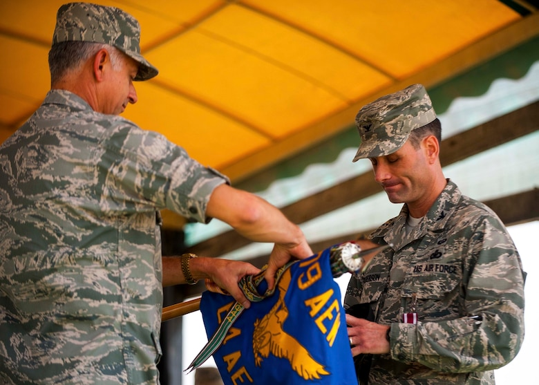 U.S. Air Force Brig. Gen. Roger H. Watkins, 379th Air Expeditionary Wing commander, and Col. Gregory Anderson, 64th Air Expeditionary Group commander, roll the 64th AEG guidon during an deactivation ceremony at an undisclosed location in Southwest Asia, May 1, 2014. The 64th AEG was activated in September 2005, and was deactivated in part of a downsizing in the region. (U.S. Air Force photo by Master Sgt. Jason Kauffung)