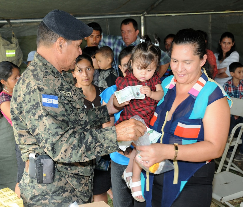 A Honduran woman and her child receives vitamins and medicine from a Honduran military service member during a Medical Readiness Training Exercise (MEDRETE) May 8.  The MEDRETE was conducted by Joint Task Force-Bravo's Medical Element, with support from the JTF-Bravo Joint Security Forces and Army Forces Battalion, in partnership with the Honduran Ministry of Health and the Honduran military to provide medical care to more than 720 people in the remote village of La Arena in the Copan region of Honduras.  The team worked together to provide preventative medicine to the villagers, including classes on hygiene, preventative dental care and nutrition.  They also provided immunizations to children, dental care, wellness checkups, medications and minor medical procedures.  (Photo by U. S. Air National Guard Capt. Steven Stubbs)