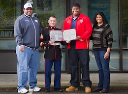 Marcus Griffin (third from left), a standout defensive lineman for the Bellevue High School Wolverines and 18-year-old native of Bellevue, Wash., stands alongside his parents and accepts a Semper Fidelis All-American Bowl certificate of commendation from Sgt. Christopher Noury (second from left), a career counselor with Marine Corps Recruiting Substation Bellevue, during a ceremony at Marine Corps Recruiting Substation Bellevue, Wash., May 9, 2014. Griffin was among 90 student athletes selected as Semper Fi All-Americans for their dedication to the community, classroom and on the gridiron. Griffin was the sole Washington State student selected to participate in the Semper Fidelis All-American Bowl at the StubHub Center in Carson, Calif., Jan. 5. In June, Griffin will begin attending the University of Arizona on a football scholarship.(U.S. Marine Corps photo by Sgt. Reece Lodder)