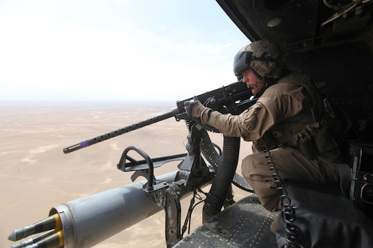 """Corporal Andrew Harris, a UH-1Y Huey crew chief with Marine Light Attack Helicopter Squadron 369, and a Highland, Illinois, native, performs a weapons check before an aerial assault support mission for ground convoys in Helmand province, Afghanistan, May 3, 2014. Before the last Marines and sailors of Forward Operating Bases Nolay and Sabit Qadam convoyed out of northern Helmand to return to Camp Leatherneck for the final time, the """"Gunfighters"""" of HMLA-369 and """"Heavyweights"""" of Marine Heavy Helicopter Squadron 466 provided overwatch for returning vehicle convoys as well as retrograde support."""