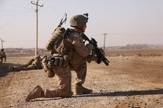 Corporal Brendan O'Bryant, a team leader with 1st Platoon, Company K, 3rd Battalion, 5th Marine Regiment, kneels during a security patrol here, Dec. 22. The Marines frequently patrol from the company's position to a recently established patrol base to keep the road clear of improvised explosive devices and monitor changes in the area.