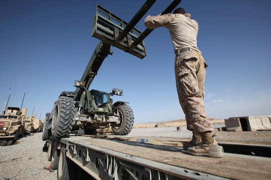 A Marine with Combat Logistics Battalion 7 signals down while loading a Tractor, Rubber-Tired, Articulated Steering, Multi-Purpose vehicle during the final retrograde operation aboard Forward Operating Base Nolay, Afghanistan, May 4, 2014. Following four years of Marines fighting in the Sangin District and advising their Afghan counterparts, Marines left Sangin for the final time, May 4, 2014.