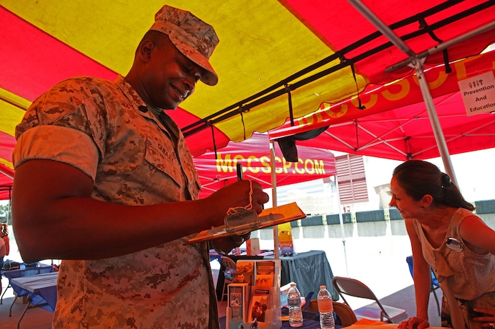 Jamil Dudley, a Nuclear, Biological, Chemical warfare specialist with CLR-1, 1st MLG, and a native of Patterson, N.J., signs up for a prevention and education course during Operation Parenthood aboard Camp Pendleton, Calif., May 1, 2014. Operation Parenthood is a one day event designed to help promote the health, well-being and safety of military families who are expecting a baby or have young children. This year, families from throughout 1st MLG participated in an event which focused on educating parents on topics like parental guidance, mood and anxiety disorders, available summer camps, daycares, life guard training, single father resources, health care, schooling and family counseling.