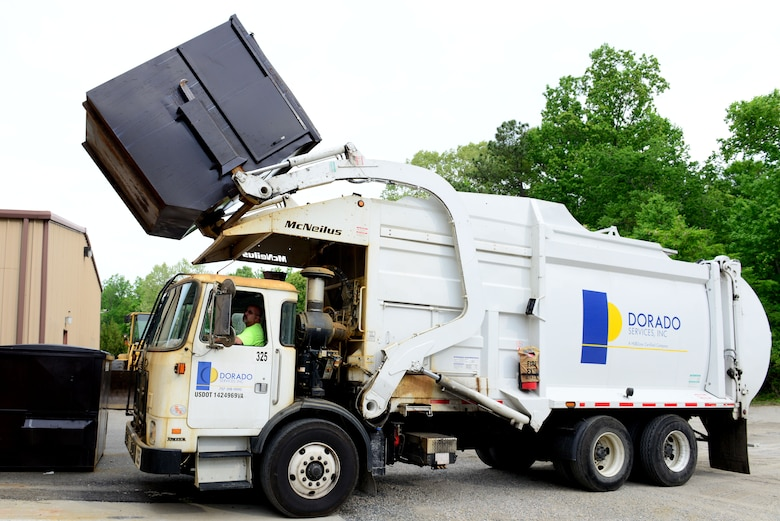 A front-loading garbage truck extracts waste from a dumpster at Fort Eustis, Va., May 7, 2014. More than 100 dumpsters are emptied daily. U.S. Air Force photo by Airman 1st Class Kimberly Nagle/Released)(Photo was cropped, levels were used and sharpened.)