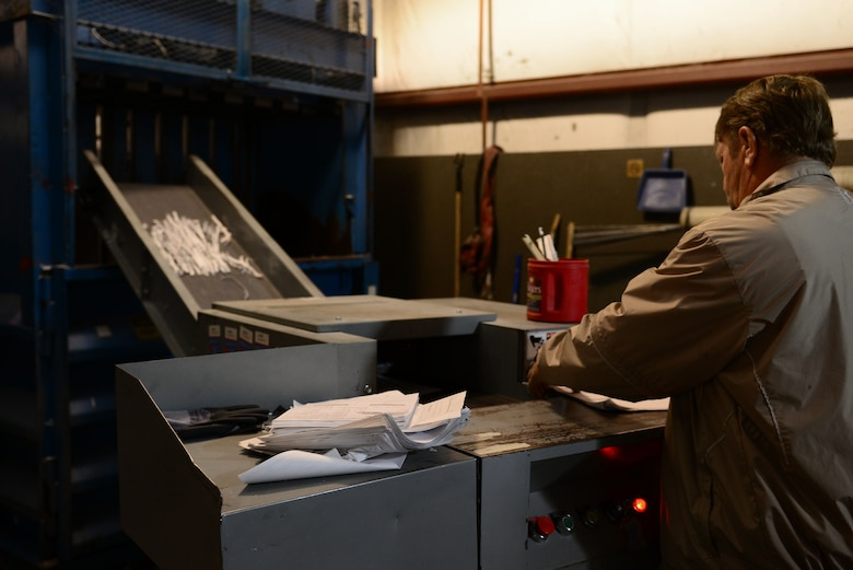 Thomas Gunter, 733rd Civil Engineering Division contracting officer representative, shreds paper at the Solid Waste and Recycle Center at Fort Eustis, Va., May 7, 2014. The SWRC has both a paper shredder and designator for classified and secret documents. Gunter hails from Berwick, Pa. (U.S. Air Force photo by Airman 1st Class Kimberly Nagle/Released)(Photo was cropped, color corrected and sharpened.)