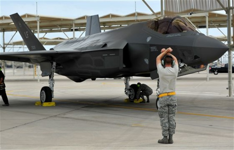Senior Airman Paul Swanson marshals in a F-35 Lightning II after one of its first sorties May 6, 2014 at Luke Air Force Base, Ariz. Swanson is a 61st Aircraft Maintenance Unit crew chief. (U.S. Air Force photo/Senior Airman Jason Colbert)