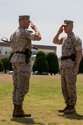 Sgt. Maj. David M. Reaves, right, the outbound sergeant major for Marine Aircraft Group 12, salutes Col. Hunter H. Hobson, the commanding officer for MAG-12, after relinquishing control of the sword of office, May 6, 2014, during a post and relief ceremony aboard Marine Corps Air Station Iwakuni, Japan. The ceremony marks the end of Reaves' tour as MAG-12 sergeant major.