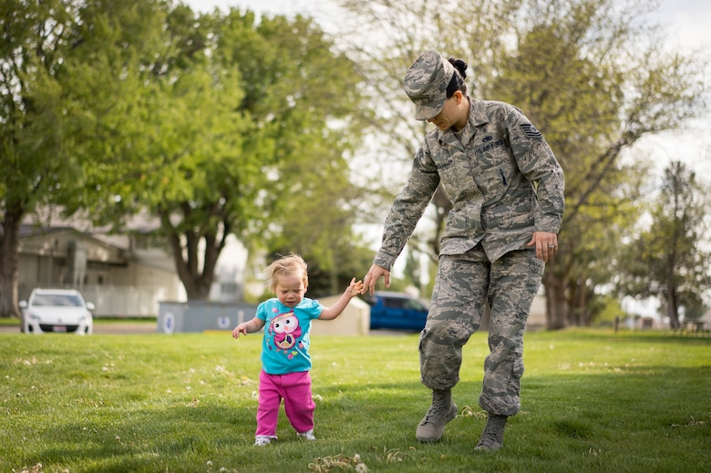 Oleksandra Valley, daughter of Tech. Sgt. Jamie Meadows-Valley from the 366th Aerospace Medicine Squadron, cautiously lets go of her mother's hand while trying to walk at Mountain Home Air Force Base, Idaho, on May 6, 2014. Since being adopted from a Ukrainian orphanage, Oleksandra has thrived, learning to walk and feed herself. (U.S. Air Force photo/Tech. Sgt. Samuel Morse)