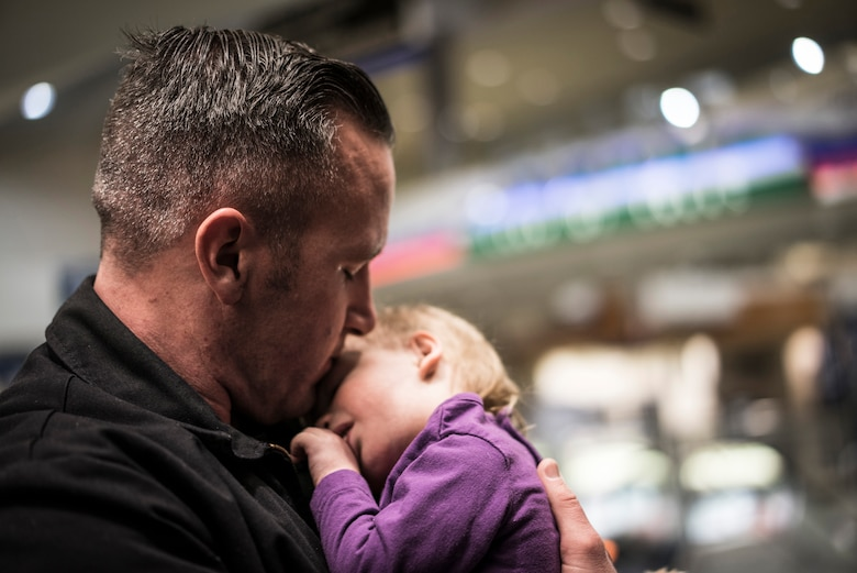 Master Sgt. Ernie Valley cradles his new daughter, Oleksandra, after greeting her at the Boise Airport, Boise, Idaho, on Jan. 23, 2014. Despite not seeing each other for several weeks, Oleksandra immediately appeared to be at home in her new father's arms. (U.S. Air Force photo/Tech. Sgt. Samuel Morse)