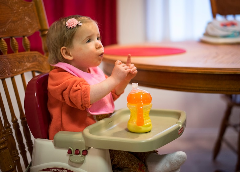 "Oleksandra Valley, 2, makes the sign language gesture for ""more,"" indicating she wants more food, at the Valley residence in Mountain Home, Idaho. In a week, she went from being spoon-fed at a Ukrainian orphanage to communicating her desire for more food through sign language and beginning to feed herself. (U.S. Air Force photo/Tech. Sgt. Samuel Morse)"
