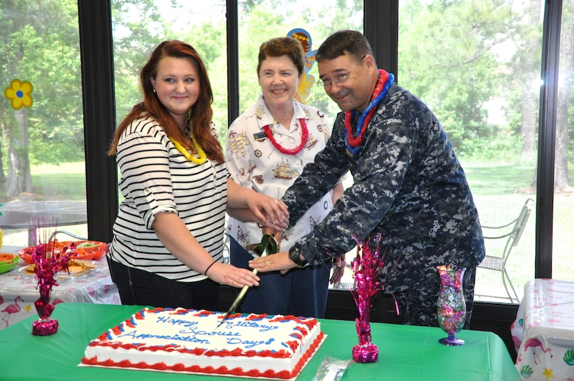 Jan Hill, representing the Navy Wife's Club of America (center), Navy spouse Jecie Chipman, and Cmdr. David Tarwater, Naval Support Activity executive officer, cut a cake in honor of Military Spouse Appreciation Month during a Cake and Ice Cream Social May 9, 2014, at the Fleet & Family Support Center, on Joint Base Charleston – Weapons Station. (U.S. Navy photo/ Kris Patterson)