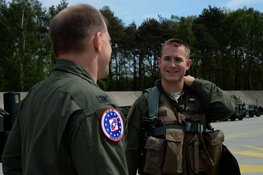 U.S. Air Force Col. Robert Winkler, 52nd Operations Group commander, left, speaks with Capt. Anthony Kiggins, a 480th Fighter Squadron pilot, on the flightline at Łask Air Base, Poland, May 7, 2014. Winkler visited with 480th FS pilots who flew F-16 Fighting Falcon aircraft from their home station at Spangdahlem Air Base, Germany, to Łask. (U.S. Air Force photo by Staff Sgt. Joe W. McFadden/Released)