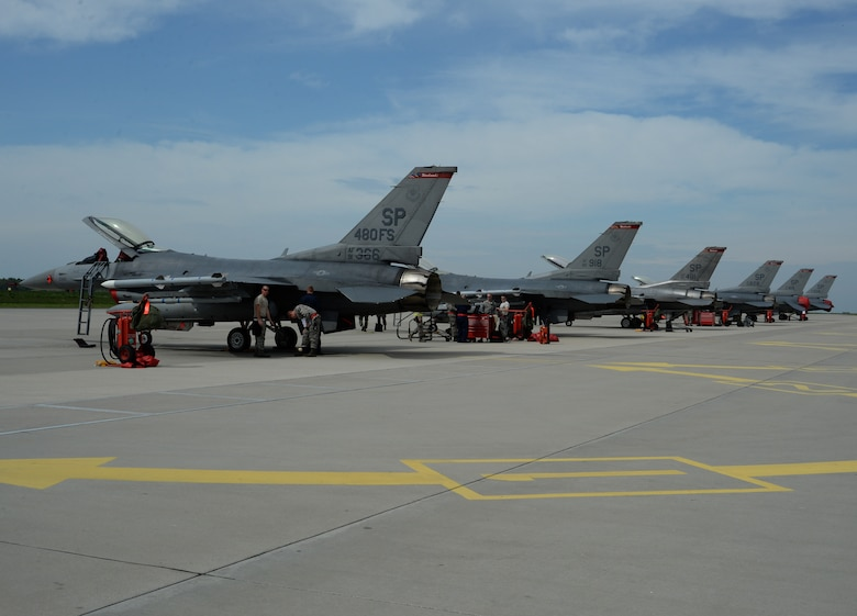 Six F-16 Fighting Falcon fighter aircraft assigned to the 480th Fighter Squadron receive maintenance while on the flightline at Łask Air Base, Poland, May 7, 2014. The 480th FS, known as the Warhawks, maintain a lineage of flying service going back more than 50 years. (U.S. Air Force photo illustration by Staff Sgt. Joe W. McFadden/Released)