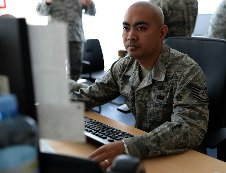 U.S. Air Force Tech. Sgt. Rommel Delmundo, Detachment 1, 52nd Operations Group contracting officer and Las Vegas native, reads an email while at his desk at Łask Air Base, Poland, May 7, 2014. The mission of Detachment 1 serves to foster bilateral defense ties, enhance regional security and increase interoperability among NATO allies through combined training exercises with periodic rotational aircraft. (U.S. Air Force photo by Staff Sgt. Joe W. McFadden/Released)